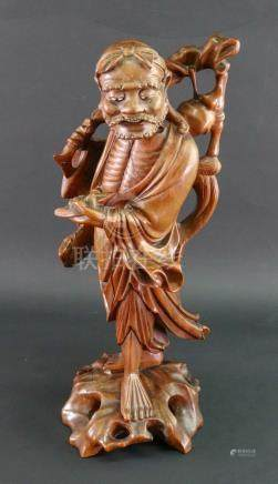 A Chinese carved wood figure of a man carrying a branch over his shoulder, 20th century, 38cm high.