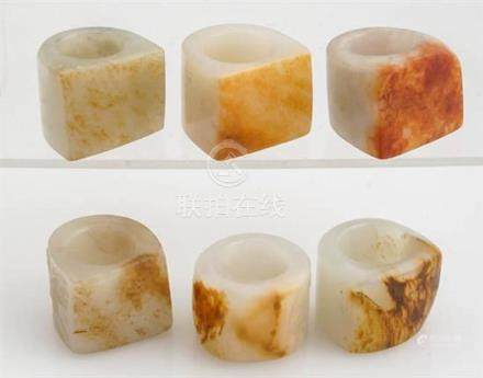 Six Chinese Russet-White and Pale-Celadon Jade Archer's Thum