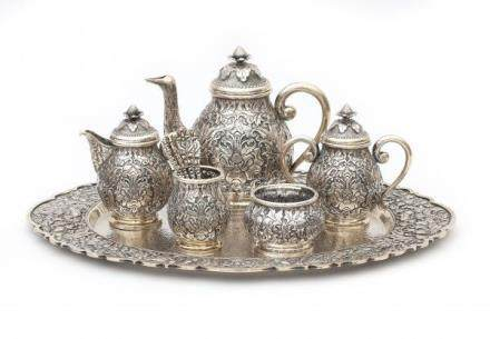 A Djokja silver tea set decorated with stylized flowers. The set comprises of; a teapot, lidded