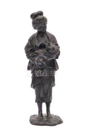 A Japanese bronze sculpture, a mother holding her child and carrying a tetsubin. Signed on base with