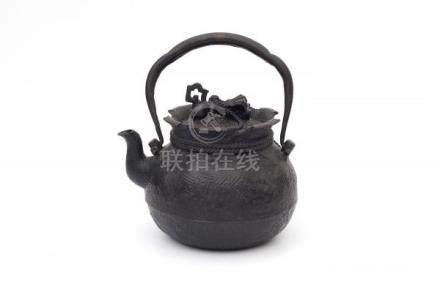 A Japanese cast iron water pot, in the shape of a tied burlap sack. Marked on the handle. Meiji