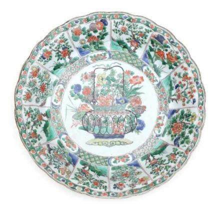 A Chinese famille verte charger, decorated with flowerbasket surrounded with panels of flowers.