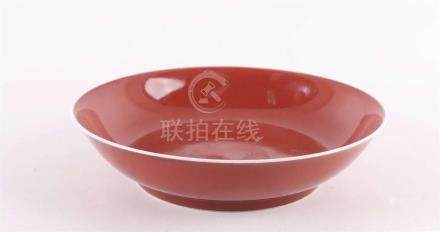 A red glazed porcelain dish on a stand ring, China, 19th / 2