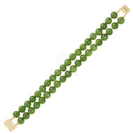 A JADE BEAD BRACELET in 14ct yellow gold, comprising of