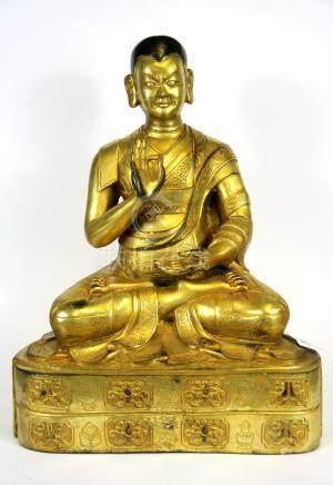 A large Tibetan gilt bronze figure of seated deity, H. 30cm.