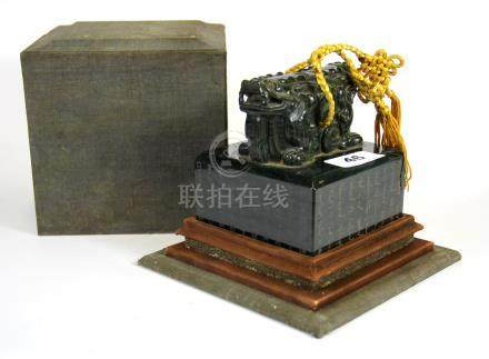 A fine Chinese hand carved jade seal mounted with a two headed lion and resting on a wooden stand