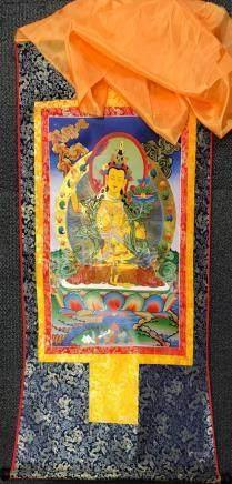 A Tibetan silk mounted thangka, W. 82cm L. 125cm.