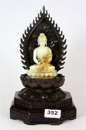 A Chinese carved jade figure of the seated Buddha on a carved hardwood stand, overall H. 28cm.