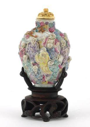 Good Chinese porcelain relief snuff bottle with ivory stopper, raised on a carved hardwood stand,