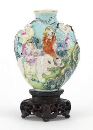 Chinese porcelain relief snuff bottle raised on a carved hardwood stand, hand painted in the famille