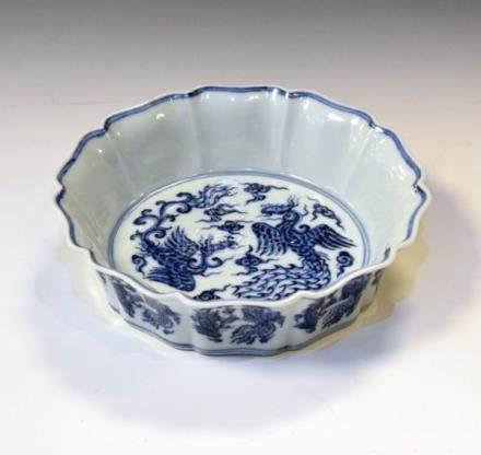 Chinese circular bowl having a ruffled rim, blue and white decoration depicting phoenix amongst