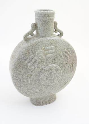 A large Chinese crackle glaze celadon twin handled moon flask having central medallion surrounded