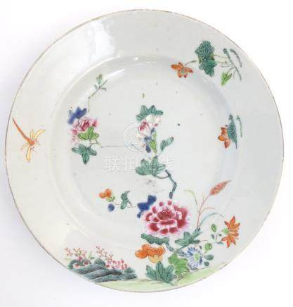 "A Chinese plate decorated with flowers, a dragonfly and a rocky outcrop. Approx. 8 3/4"" diameter."
