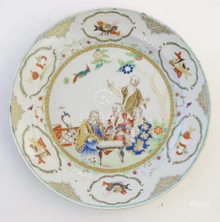 A Chinese famille verte plate with gilt highlights, decorated with four figures in a garden,