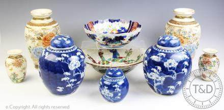 A pair of Chinese blue and white ginger jars and covers, decorated with prunus, 20cm high,