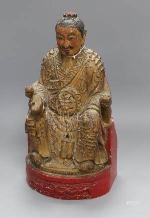 A carved wooden deity with polychrome and gilt decoration height 37cm