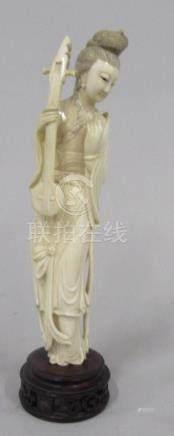 CHINE - Sculpture en ivoire à décor d'une jeune femme et cithare. Début XXe siè