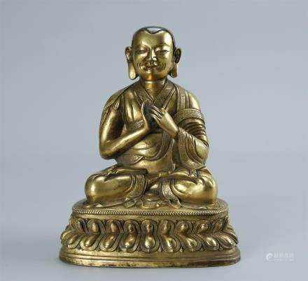 A GILT BRONZE FIGURE OF GURU BUDDHA
