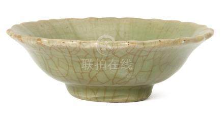 A Chinese Longquan celadon bowl, Ming dynasty, with shaped rim and impressed floral motif to central