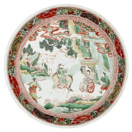 A Chinese porcelain wucai dish, 17th century, painted to the central reserve with figures travelling
