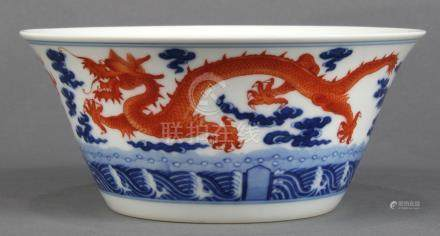 Chinese porcelain bowl, with flared walls decorated with meandering red-orange dragons amid