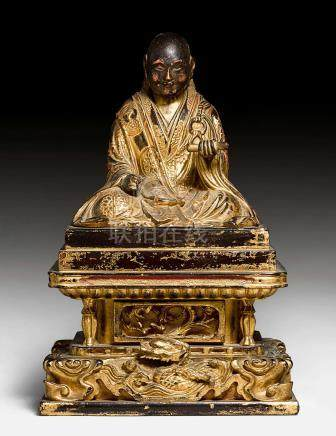 A GILT LACQUERED WOOD FIGURE OF A SEATED MONK.