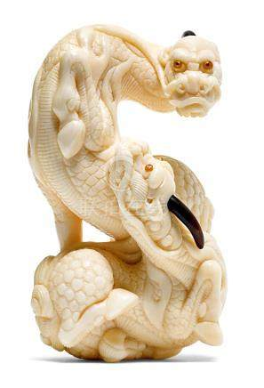 A MAMMOTH TOOTH NETSUKE CARVED AS TWO INTERTWINED KIRIN BY SAITO BISHU (*1943).