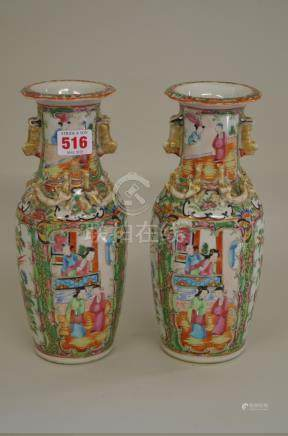 A pair of Chinese Canton famille rose twin handled vases, late 19th century, 25cm high. (2)