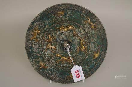 A Chinese silvered bronze and parcel gilt circular hand mirror,moulded in relief with animals,