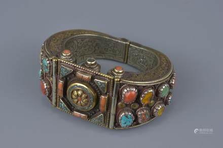 A Tibetan metal bracelet with various stone inserts.