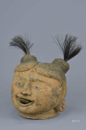 A vintage wooden puppet head with movable tongue on a string pulley.16cm height