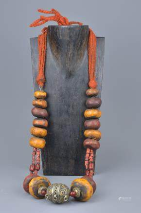 A large Moroccan amber resin and coral bead necklace with enamel silver metal pendant.