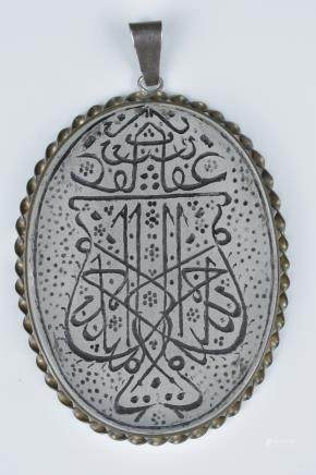 A Persian white metal pendant with inscription.