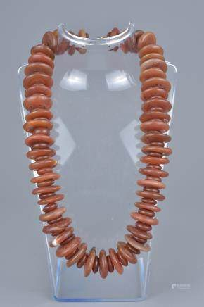 A string of red agate beads in a necklace.