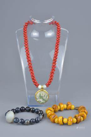 One beaded necklace with glass pendant and two beaded bracelets.