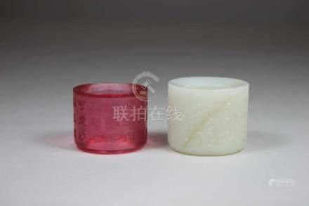 2 Daumenringe, China, einer weisse Jade und einer in pinkem Glas mit geritzten Schriftzeichen, D.: