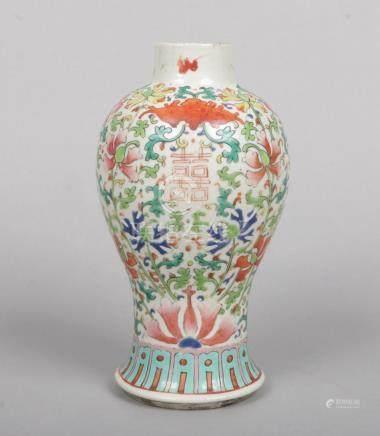 A 19th century Chinese baluster shaped vase. Painted in coloured enamels with lotus scrolls, fruit