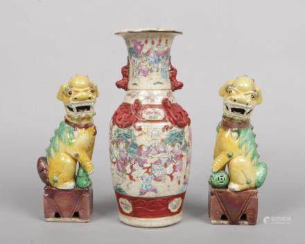 A pair of 20th century Chinese lion dogs raised on rectangular plinths and coloured in enamels along