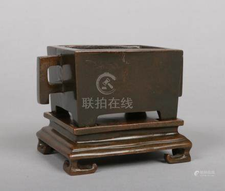 A Chinese bronze twin handled censor on stand of plain rectangular form. Four character Xuande reign
