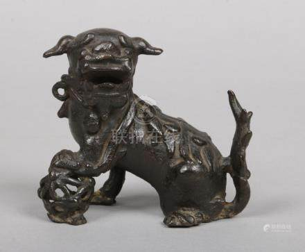 A Chinese Ming dynasty bronze model of a lion dog with a brocade ball, 9.75cm.