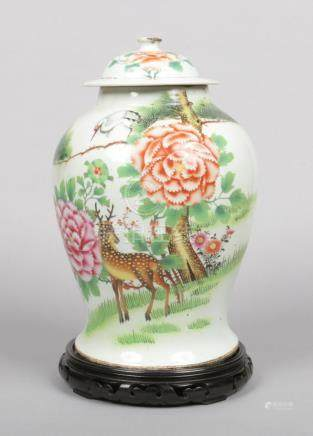 A large Chinese late 19th / early 20th century baluster shaped jar and cover raised on a hardwood