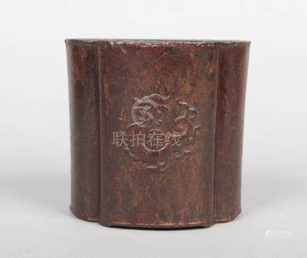 A 19th century Chinese hardwood bitong of quatrefoil shape. Carved in very light relief with a