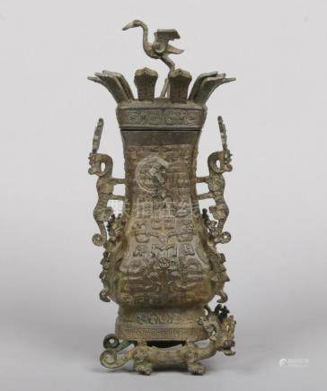 An archaistic Chinese bronze baluster shaped urn and cover. The finial formed as a standing crane,