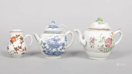 An 18th century Chinese famille rose teapot and cover along with a blue and white example and a
