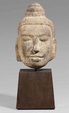 Kopf einer Gottheit. Kalkstein. Kambodscha. Ca. 11./12. Jh.Ovale Kopfform mit gesenkten Lidern,