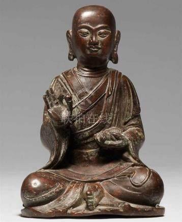Arhat Bakula. Bronze. Qing-ZeitMit untergeschlagenen Beinen sitzend, in der angehobenen rechten Hand