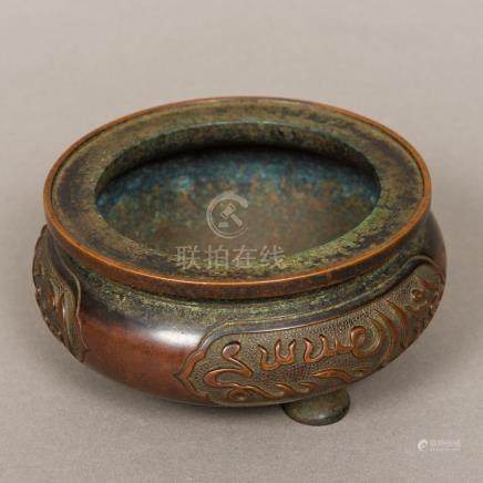 A Chinese patinated bronze censer Of three legged squat circular form,