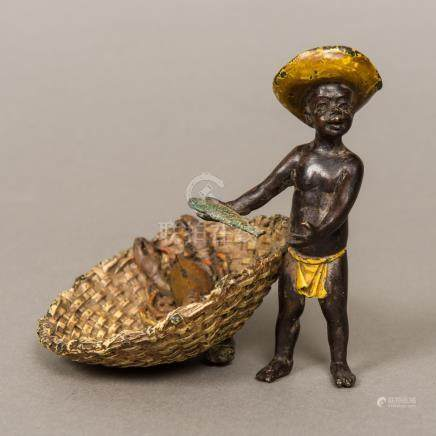 A Chinese cold painted bronze model formed as a young fisher boy holding a fish beside a basket