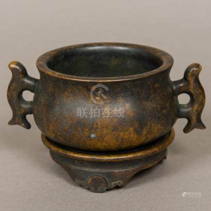 A Chinese patinated bronze censer on stand Of squat waisted circular form, with twin loop handles,