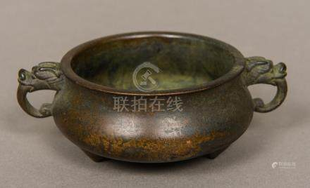A Chinese patinated bronze censer Of squat circular form with twin dragon mask handles,